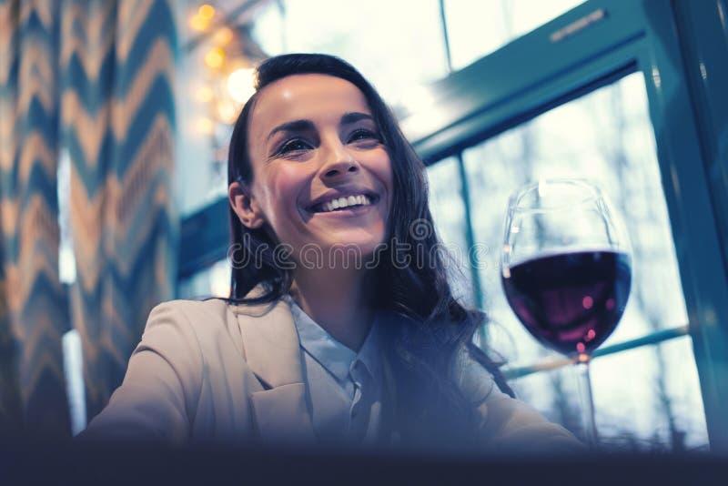 Счастливая женская персона держа улыбку на ее стороне стоковое изображение