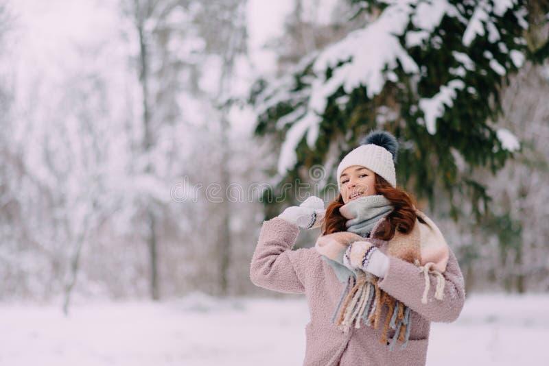 Счастливая женщина бросает снежные комья в парке стоковая фотография