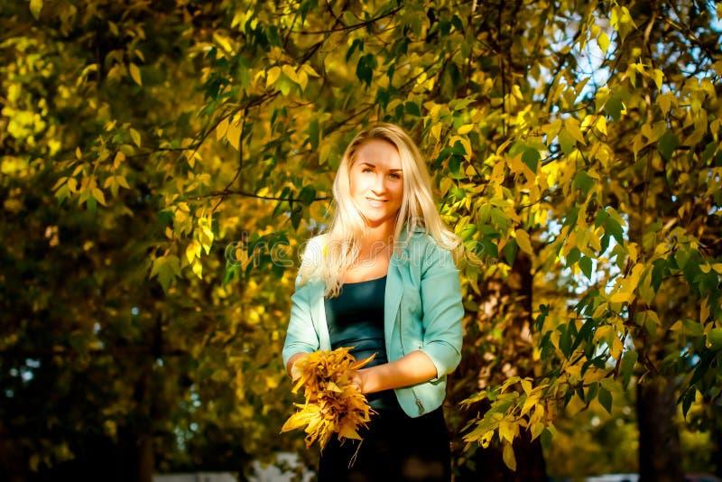 Счастливая женщина бросая вверх листья в осени, усмехаясь Радостная и возбужденная молодая женщина счастливо бросает желтые листь стоковое изображение