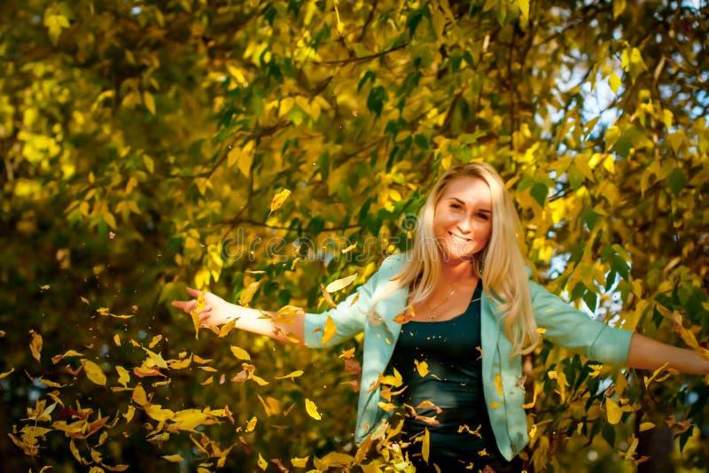 Счастливая женщина бросая вверх листья в осени, усмехаясь Радостная и возбужденная молодая женщина счастливо бросает желтые листь стоковое изображение rf