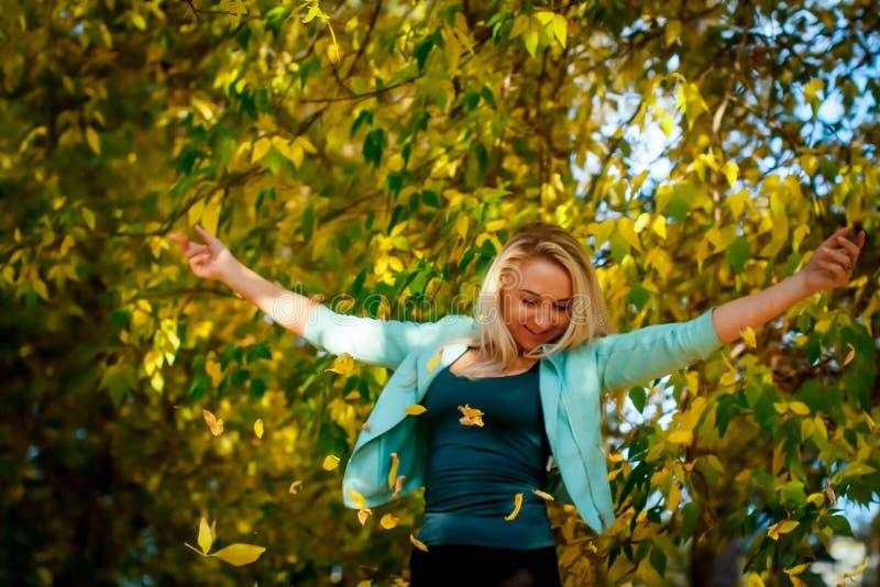 Счастливая женщина бросая вверх листья в осени, усмехаясь Радостная и возбужденная молодая женщина счастливо бросает желтые листь стоковая фотография