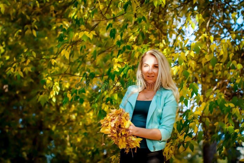 Счастливая женщина бросая вверх листья в осени, усмехаясь Радостная и возбужденная молодая женщина счастливо бросает желтые листь стоковая фотография rf