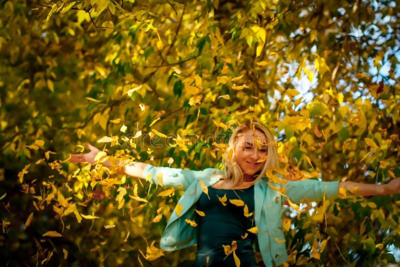 Счастливая женщина бросая вверх листья в осени, усмехаясь Радостная и возбужденная молодая женщина счастливо бросает желтые листь стоковое фото rf