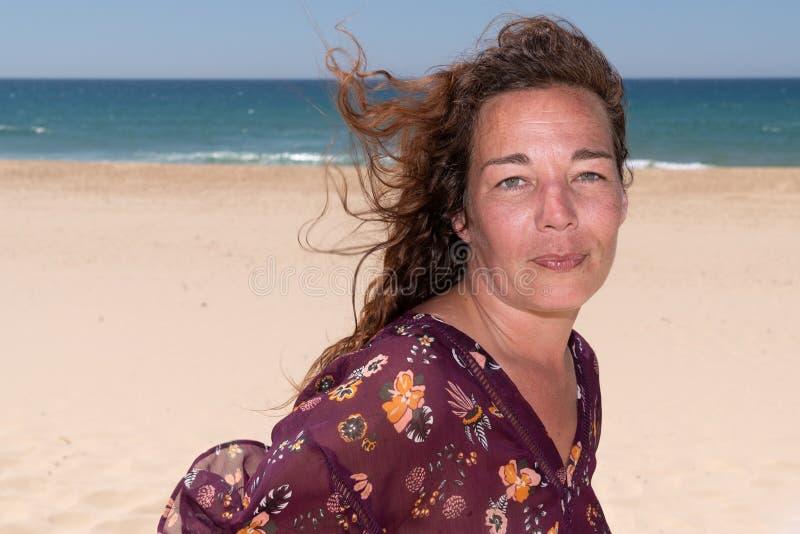 Счастливая женщина брюнета идя на ветер пляжа на волосах стоковое фото