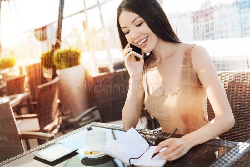 Счастливая женщина брюнет делая примечания стоковые изображения