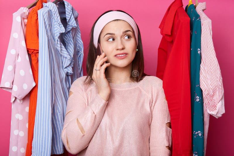 Счастливая женщина выбирает платье Девушка брюнета носит розовый свитер и диапазон волос думает о том, что-то, держит руку на щек стоковая фотография rf