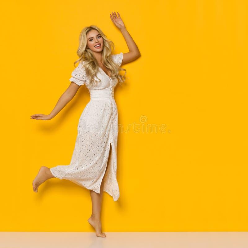 Счастливая женщина в белом платье лета танцует стоковое изображение