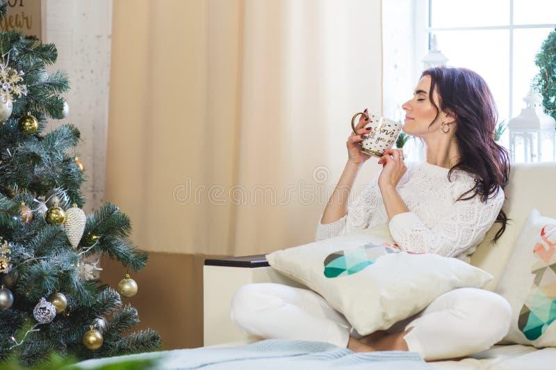 Счастливая женщина в белый связанный носить ослабляет дома для рождества стоковые изображения rf