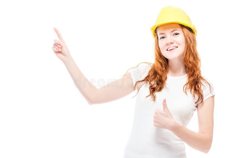 счастливая женщина в желтой трудной шляпе показывает палец стоковые изображения rf