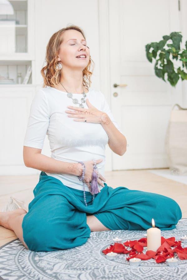 Счастливая женщина в йоге этнического костюма практикуя перед свечам стоковое фото