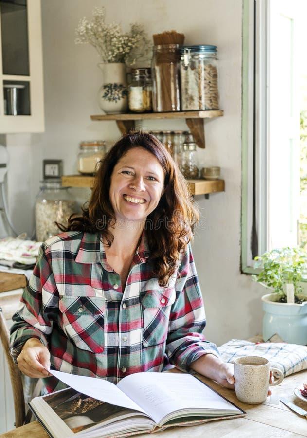 Счастливая женщина в кухне читая поваренную книгу стоковая фотография rf