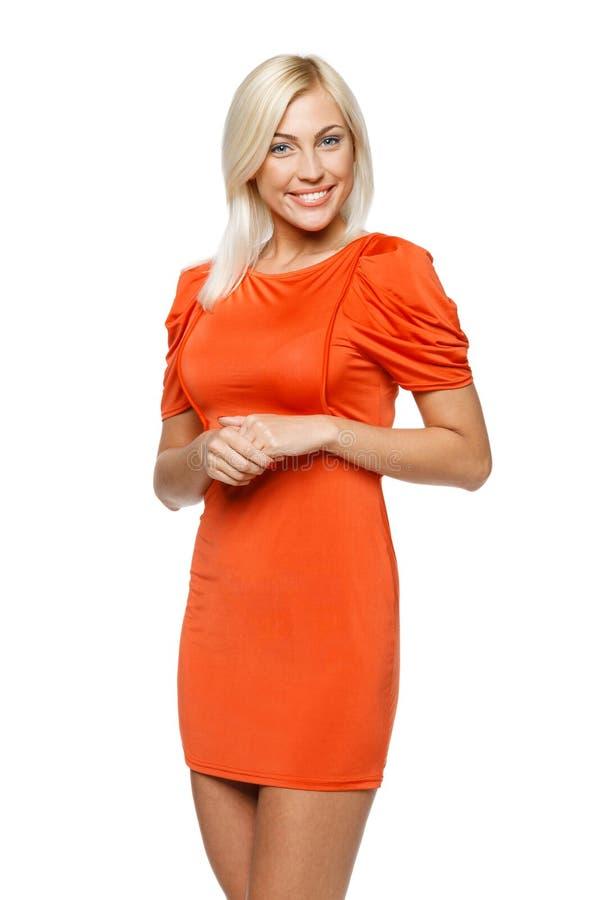 Счастливая женщина в померанцовом платье стоковая фотография