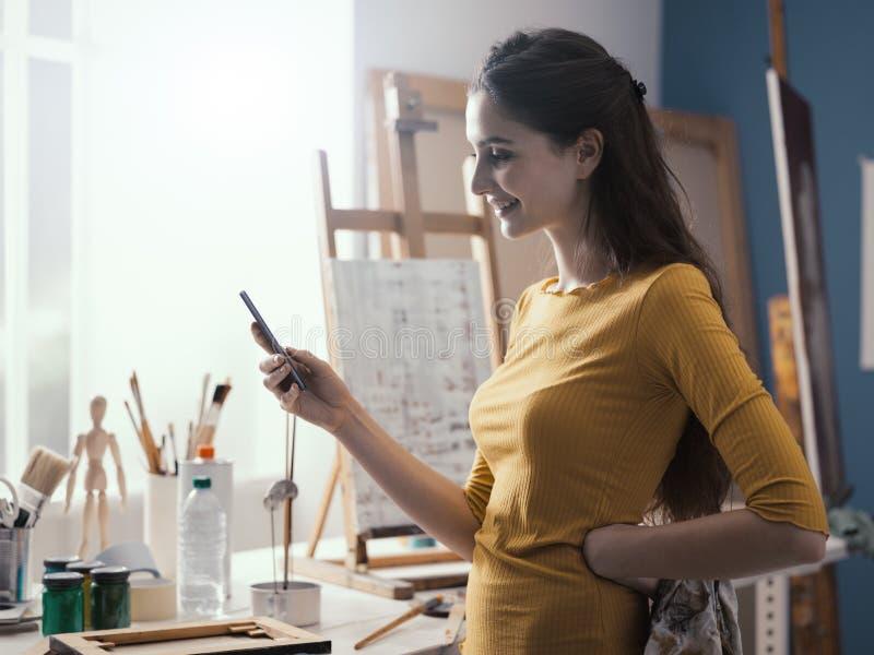 Счастливая женщина в послании студии искусства с ее телефоном стоковая фотография rf