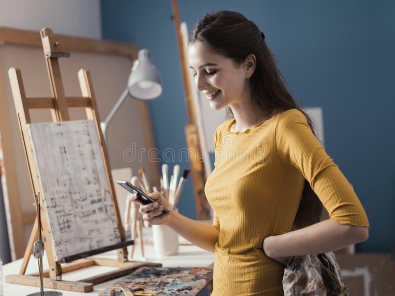 Счастливая женщина в послании студии искусства с ее телефоном стоковые изображения