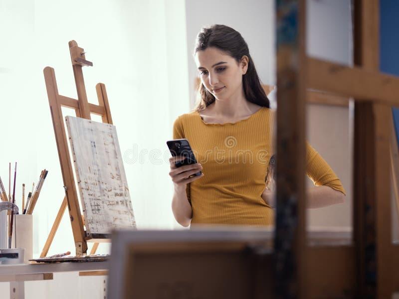 Счастливая женщина в послании студии искусства с ее телефоном стоковая фотография