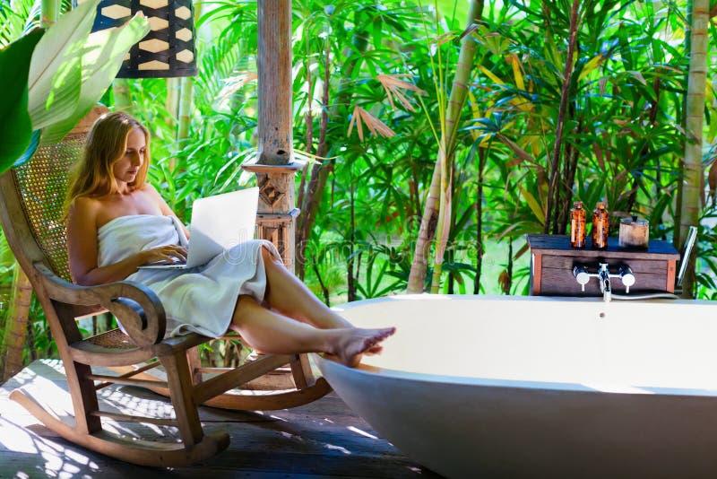 Счастливая женщина в работе ванной комнаты снаружи тропической на портативном компьютере стоковые изображения rf
