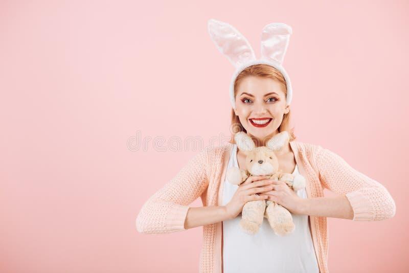 счастливая женщина в ушах зайчика с игрушкой Женщина в ушах зайчика кролика пасха счастливая Праздник весны Девушка с игрушкой за стоковые фотографии rf