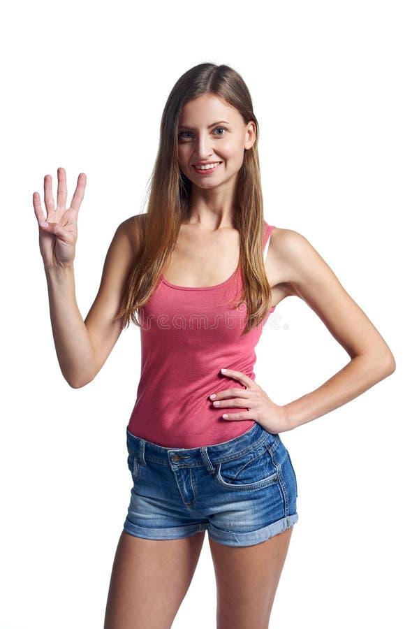 Счастливая женщина в шортах показывая 4 пальца стоковое фото rf