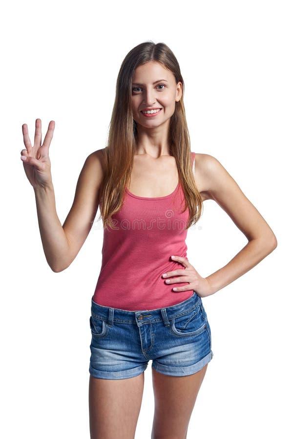 Счастливая женщина в шортах показывая 3 пальца стоковые фотографии rf