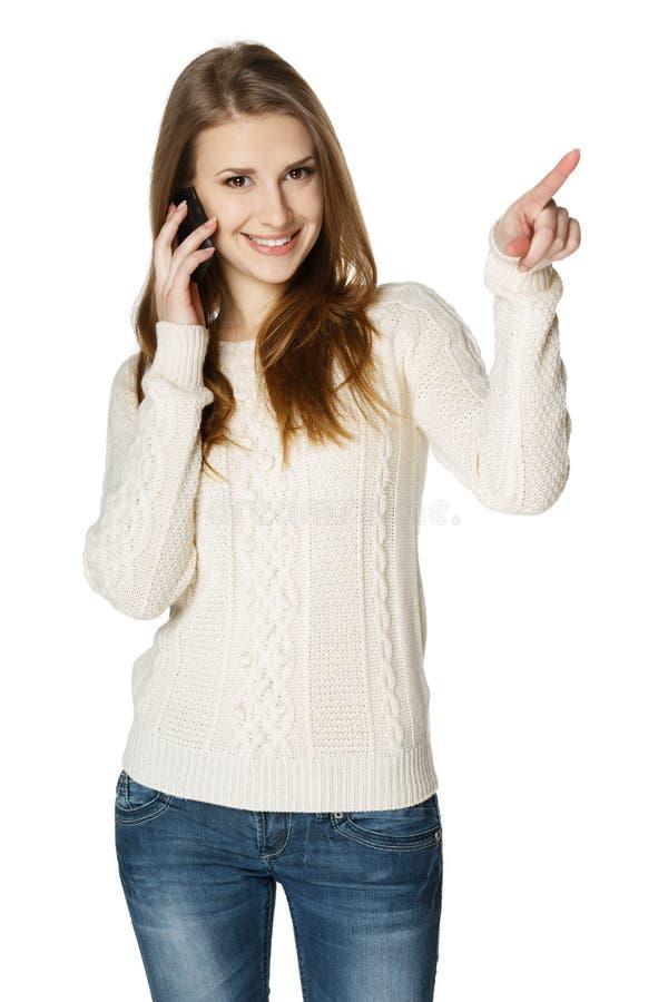 Счастливая женщина говоря на сотовом телефоне и указывая к стороне стоковая фотография rf