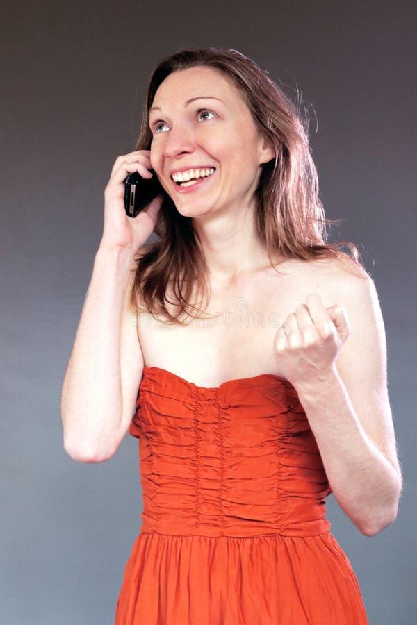 счастливая женщина говоря на хороших новостях мобильного телефона изолировала первоклассных детенышей в платье партии стоковые фото