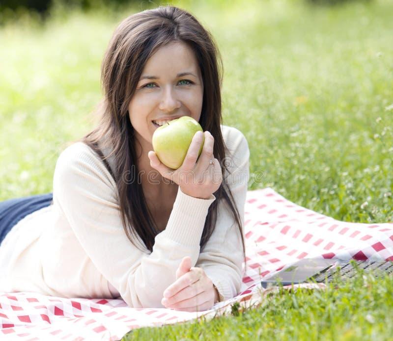 Счастливая женщина держа зеленое яблоко стоковые изображения