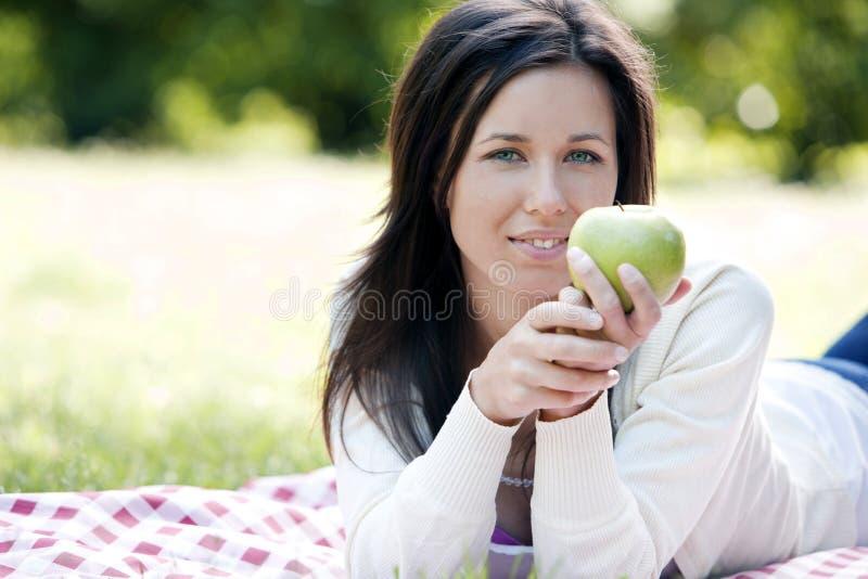 Счастливая женщина держа зеленое яблоко стоковые фото