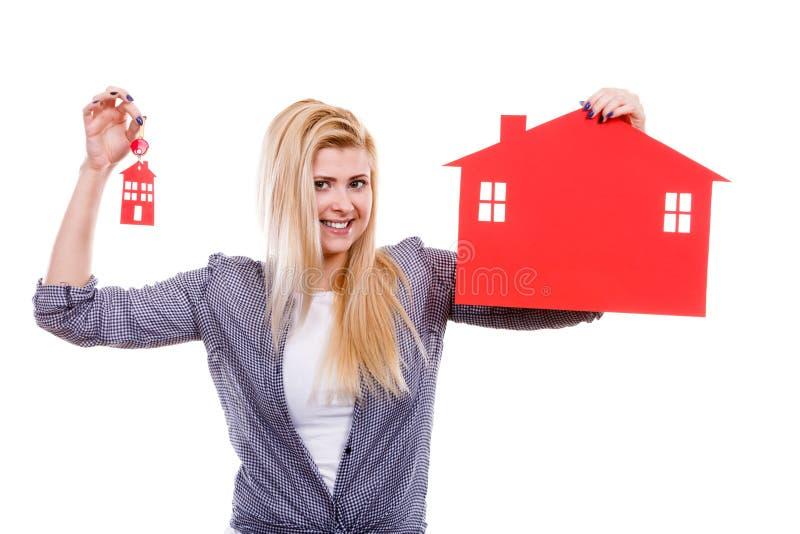 Счастливая женщина держа красный бумажный дом и ключи стоковое изображение
