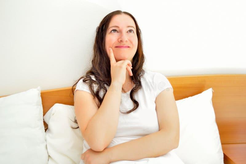 Счастливая женщина думая в кровати стоковое фото