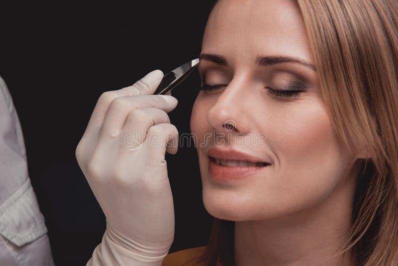 Счастливая женщина имея коррекцию брови стоковые изображения rf