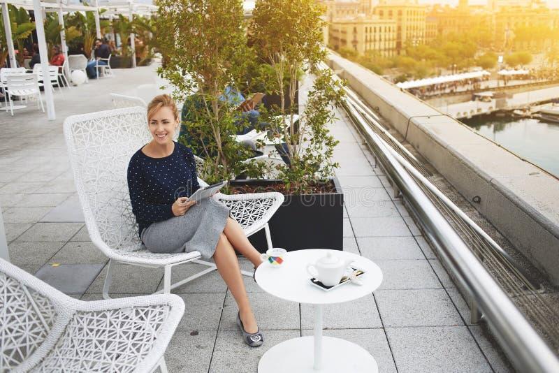 Счастливая женщина использует цифровую таблетку для проверять электронную почту, пока расслабляющий в кофейне стоковые изображения