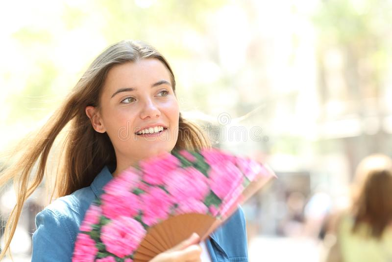 Счастливая женщина используя вентилятора идя в улице на лете стоковое фото rf