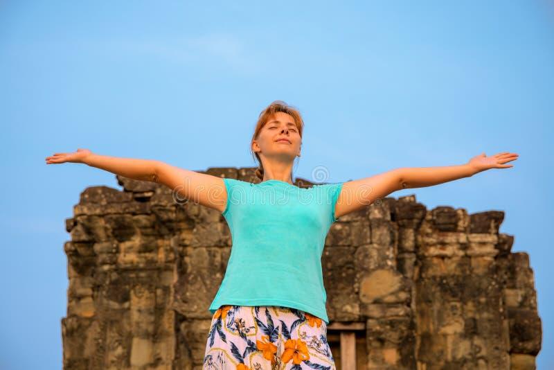 Счастливая женщина наслаждается солнцем утра na górze Temple Hill в Angkor Wat, Камбодже стоковое изображение