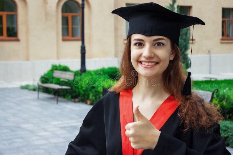 Счастливая женщина на ее университете выпускного дня Образование и люди стоковые изображения rf