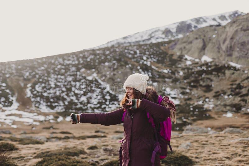 Счастливая женщина на заходе солнца в природе в осени фотографируя с мобильным телефоном потеха outdoors стоковое изображение