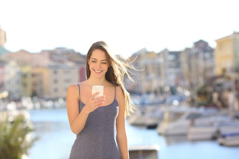 Счастливая женщина на каникулах используя умный телефон стоковые фотографии rf