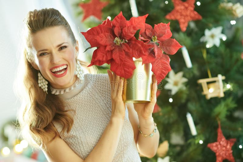 Счастливая женщина около рождественской елки показывая красный poinsettia стоковая фотография