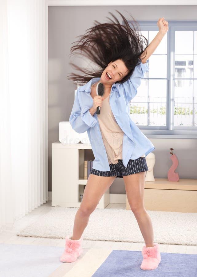 Счастливая женщина пея к hairbrush в утре стоковое изображение rf