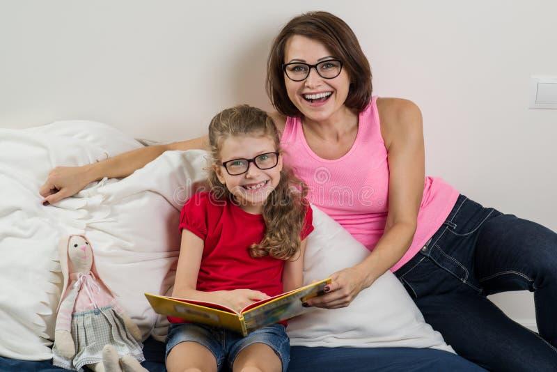 Счастливая женщина при ее ребенок дочери, читая совместно книгу a стоковая фотография