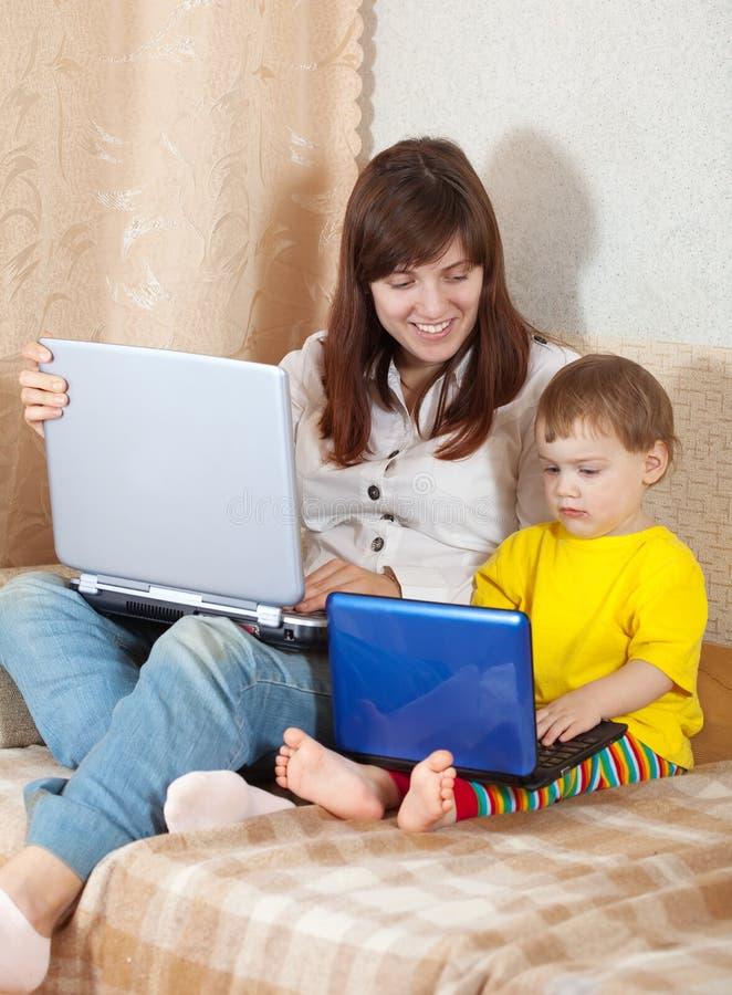 Счастливая женщина при малыш используя компьтер-книжки стоковая фотография rf