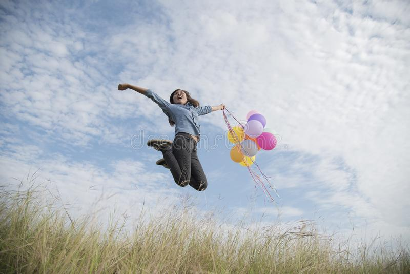 Счастливая женщина скача с воздушными шарами стоковая фотография rf