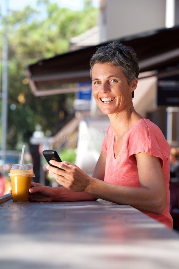 Счастливая женщина среднего возраста сидя снаружи с мобильным телефоном и питьем стоковые изображения rf
