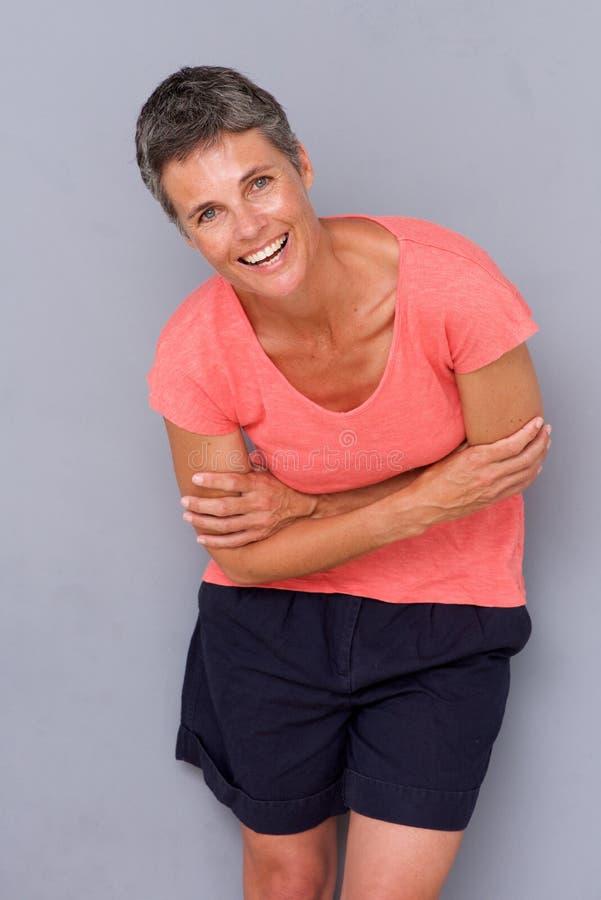 Счастливая женщина среднего возраста смеясь над серой предпосылкой стоковое фото