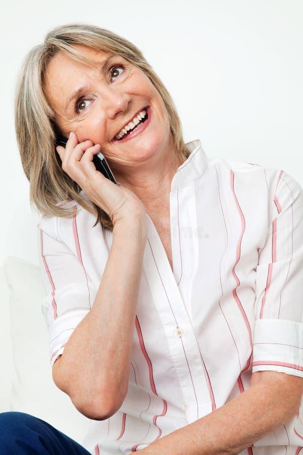 счастливая женщина старшия телефона стоковая фотография