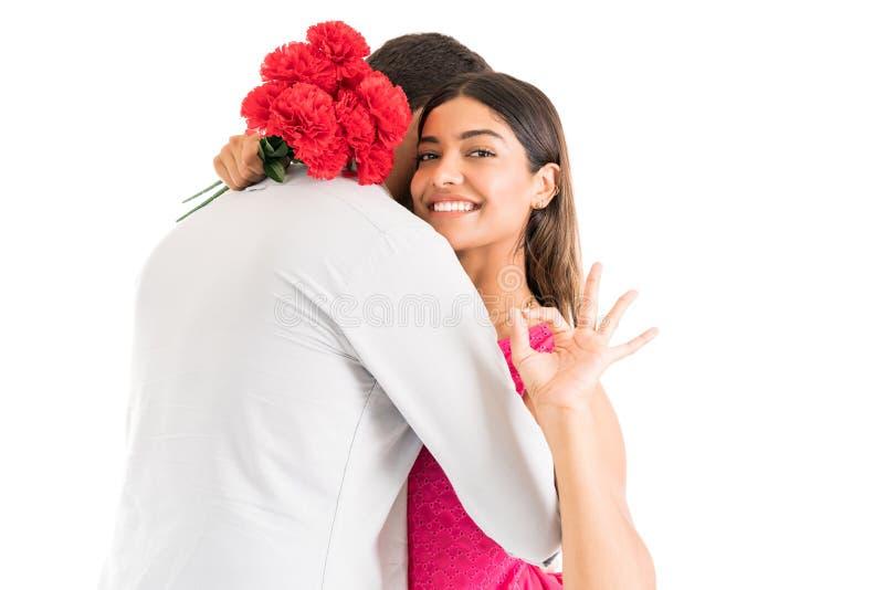Счастливая женщина с букетом обнимая человека в студии стоковые изображения