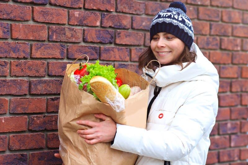 Счастливая женщина с едой в бумажной сумке в внешнем стоковые изображения