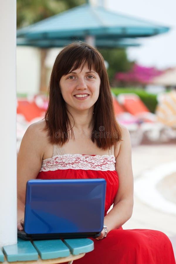 Счастливая женщина с компьтер-книжкой на курорте стоковые изображения