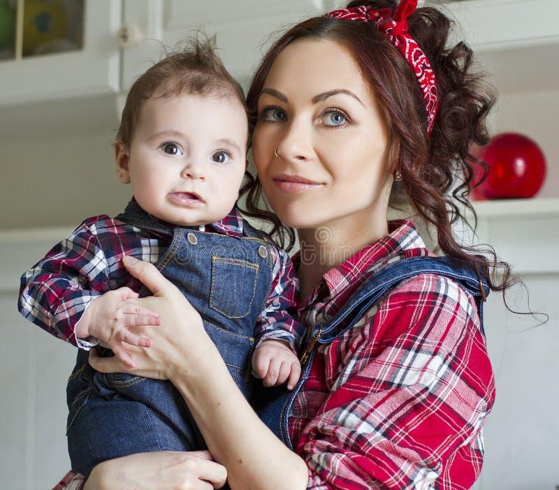 Счастливая женщина с младенцем играя в кухне стоковая фотография