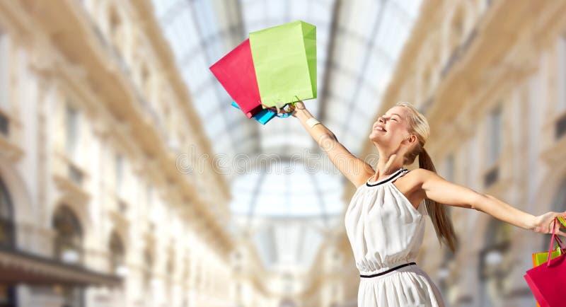 Счастливая женщина с хозяйственными сумками над торговым центром стоковые фото