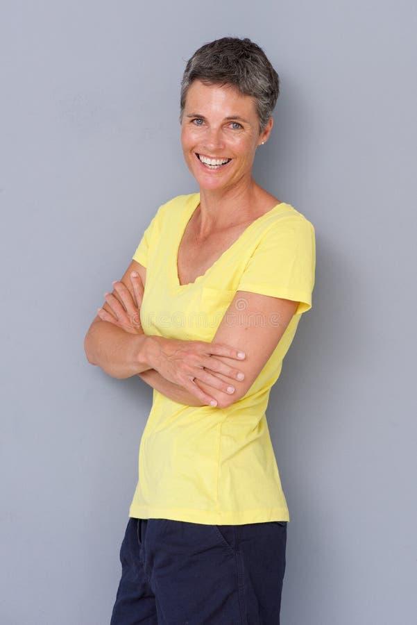 Счастливая женщина усмехаясь против серой предпосылки стоковое фото rf